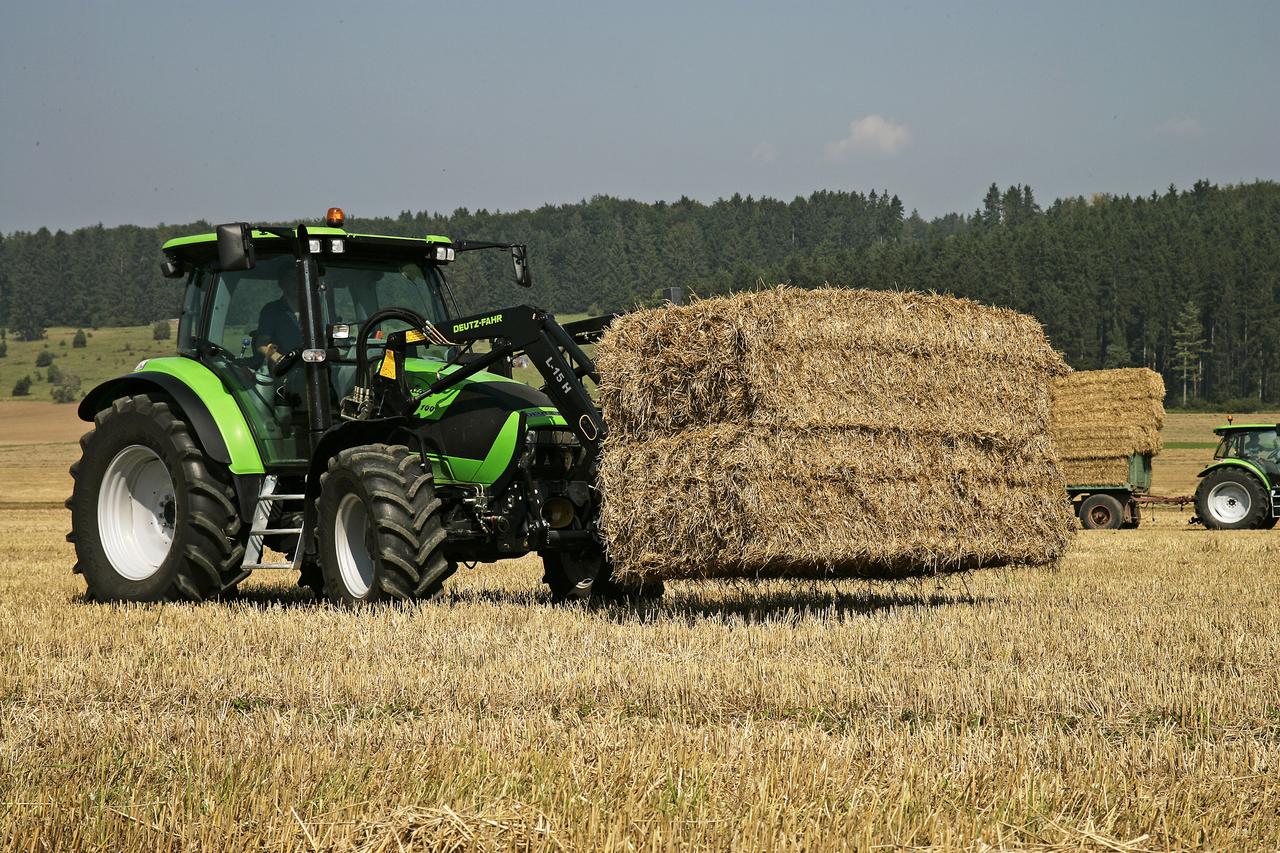 [Deutz-Fahr] trattore Agrotron K 100 al lavoro con caricatore frontale e rimorchio durante lavori di fienagione